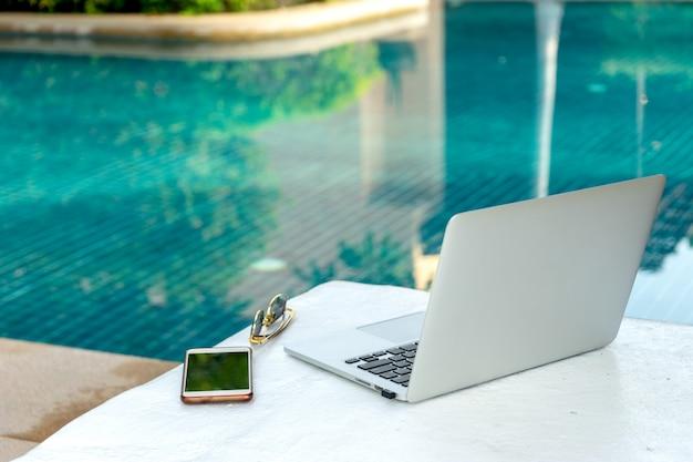 スイミングプールのそばのラップトップとスマートフォン、現代のビジネスマンはどこでも働くことができます。