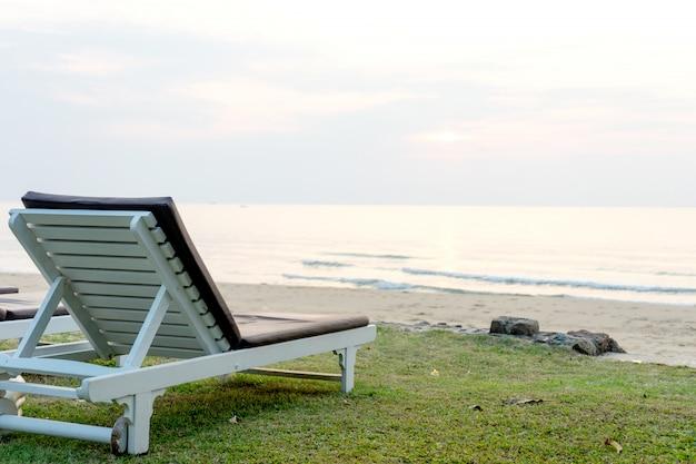 砂浜の椅子のベッド、朝の早い日の出。