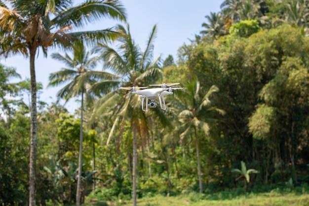 自然な緑の背景を持つ飛行ドローン