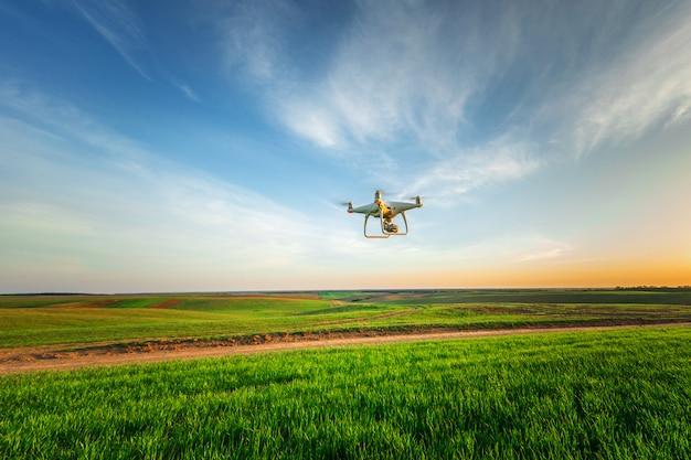 黄色のトウモロコシ畑にドローンクアッドヘリコプター