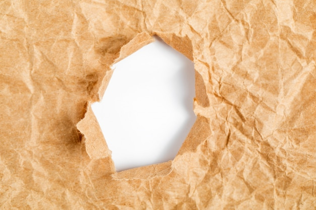 引き裂かれた側面の背景を持つ紙の穴