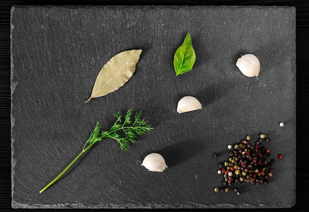 Чеснок укроп перец базилик на черном камне