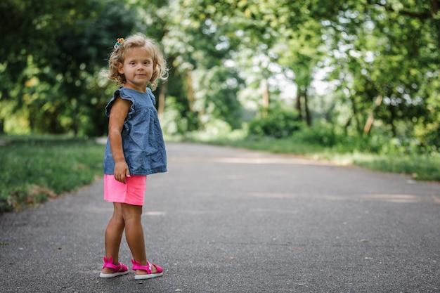 小さな女の子は公園を散歩します。