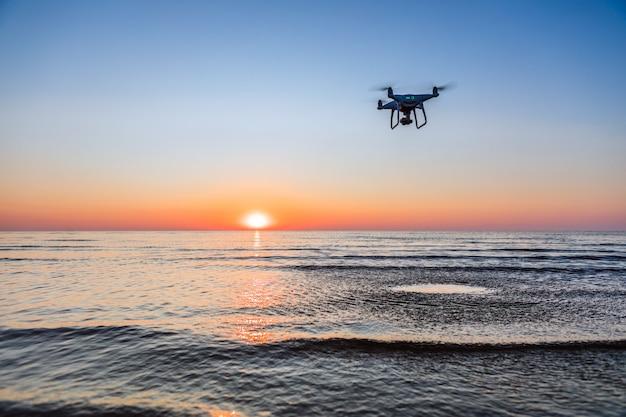 海の夕日の背景に飛行ドローン