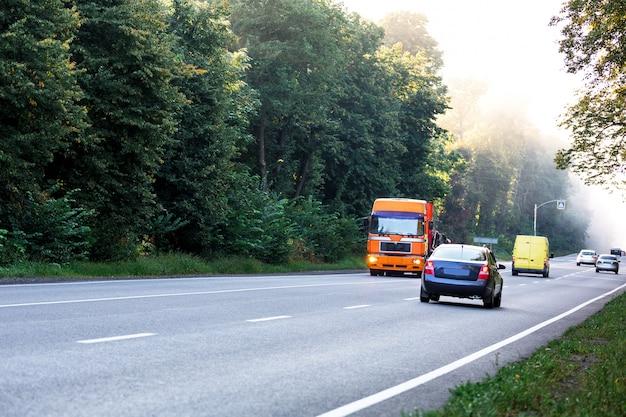 日没時の田園風景の道に白いトラックを到着