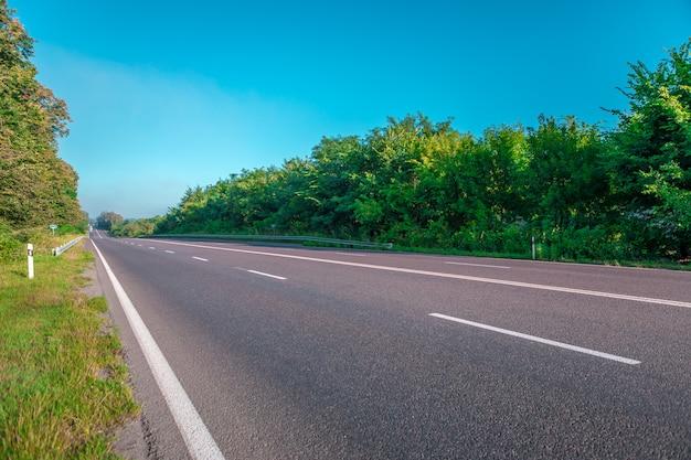 アスファルト道路と青空の下の山