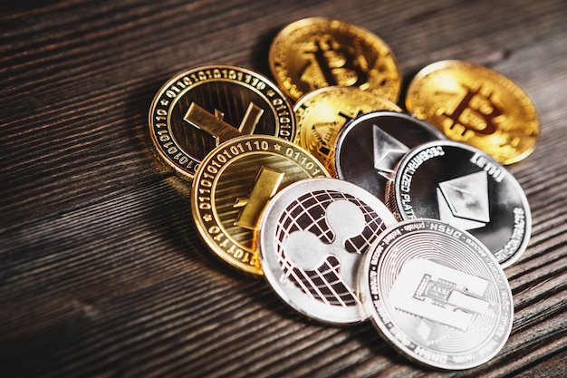 木材にビットコイン、リップル、イーサリアムシンボルと銀と黄金のコイン。