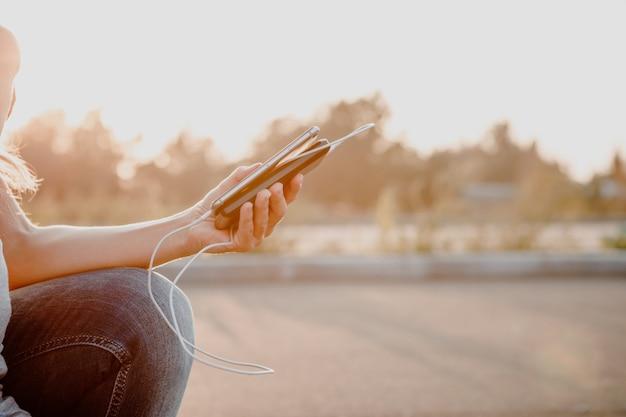 外部電源銀行からバッテリーを充電する黒いスマートフォンを保持している女性手