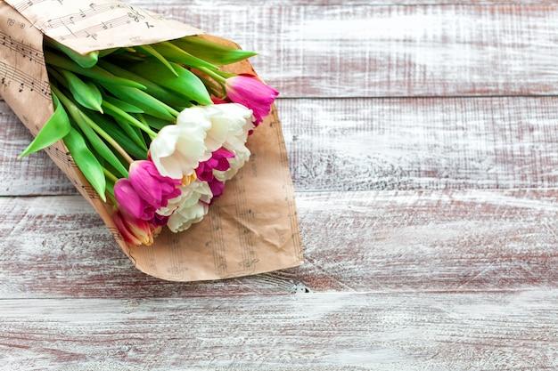 チューリップの花束は、木材の背景に分離された紙に包まれています。