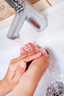 水道水で手を洗う