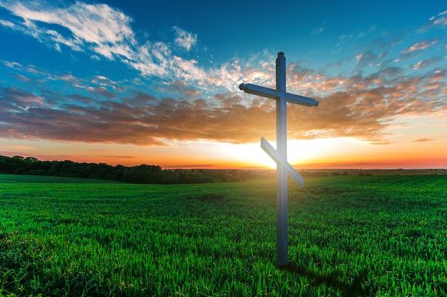 朝の緑の野原に木製の十字架。キリスト教の概念