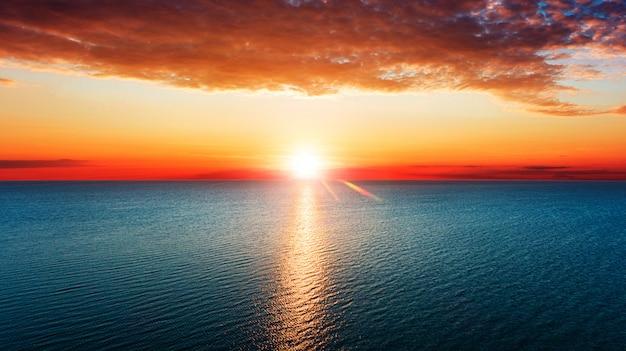 海の上に昇る太陽の空撮。