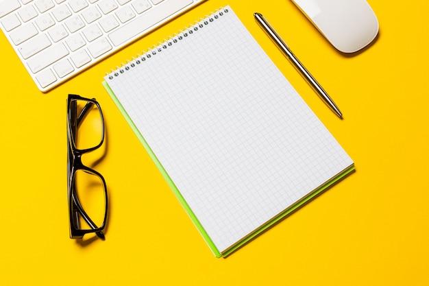 一杯のコーヒー、黄色のテーブルの空のワークスペースでビジネス作業場所の平面図です。