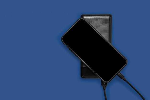 ブラックパワー銀行は、クラシックブルーパントンに分離されたスマートフォンを充電します