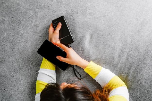 Женщина подключила зарядное устройство к телефону в офисе или дома. внешний аккумулятор.