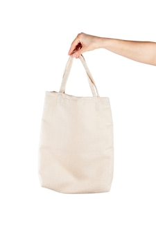 白い背景上の綿エコバッグを持つ女性。生態学または環境保護の概念。モックアップ用の白いエコバッグ