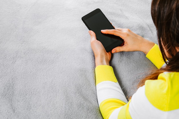 女性は、オフィスまたは自宅で電話で充電器をつないだ。パワー・バンク。