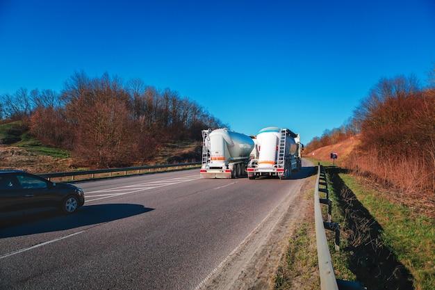 夕暮れ時の田園風景の中の道路に白いトラックを到着