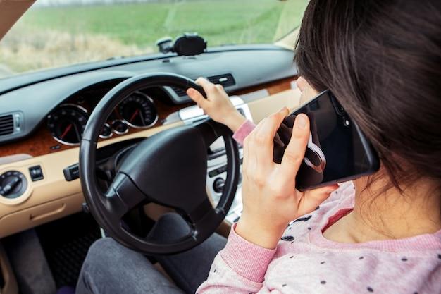車を運転中に携帯電話で話している女性