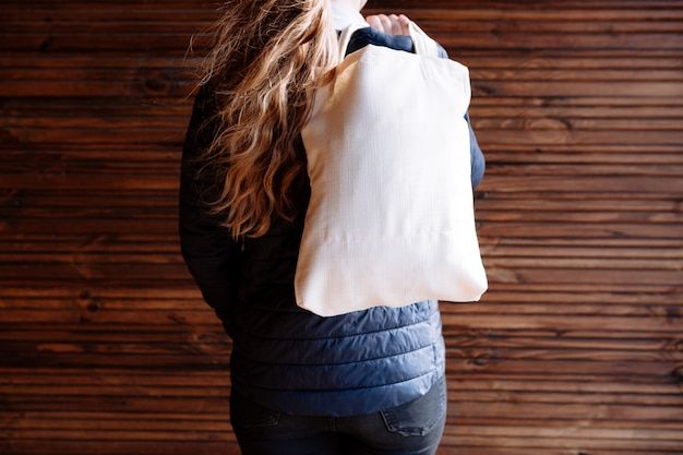 Молодая женщина, держащая белый эко сумка