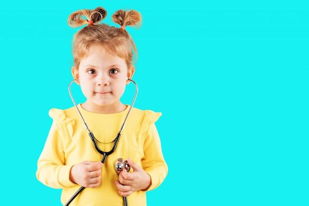 Ребенок, играющий доктора со стетоскопом в руках. счастливая усмехаясь девушка ребенк играя дома