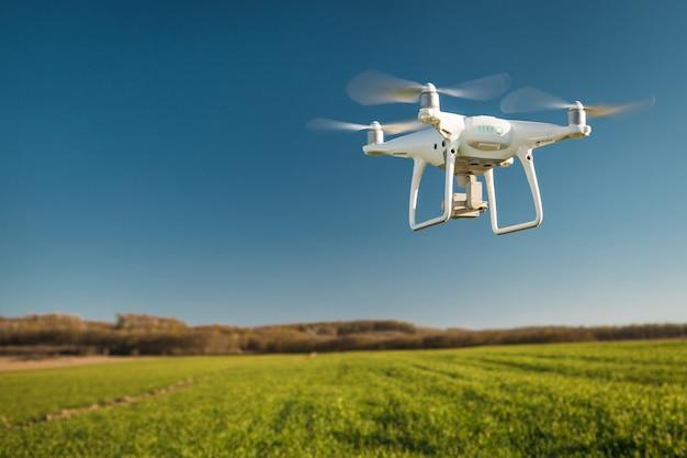 Дрон, летящий над зеленым полем