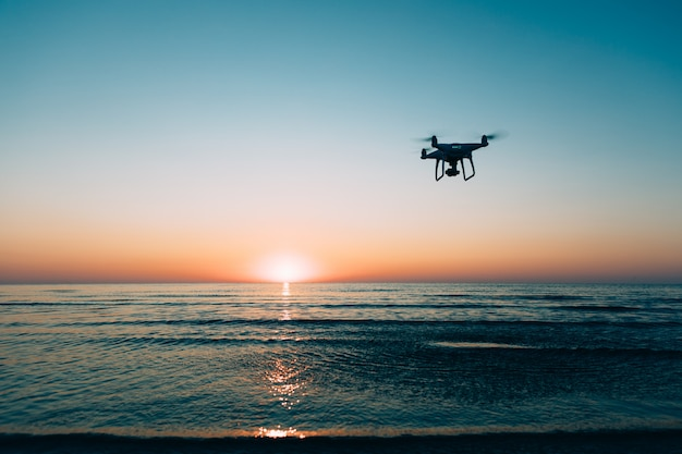 Летающий дрон на фоне морского заката
