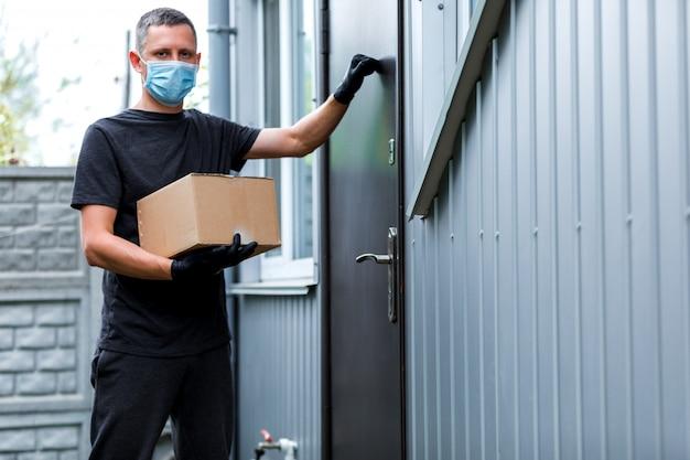 Доставка на дом, коробка для покупок, человек в перчатках и защитной маске, доставляющий посылки в дверь