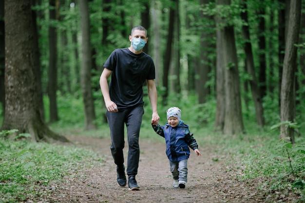 子供と医療マスクの父が公園を散歩します。