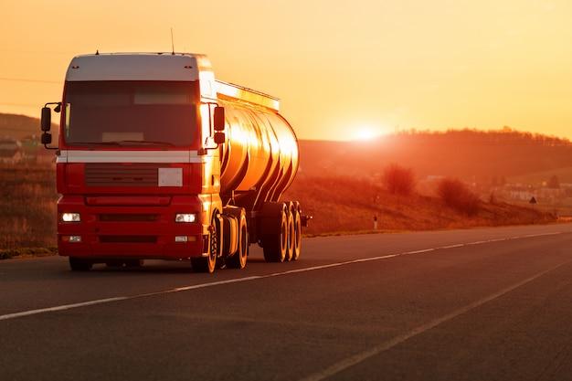 Прибывающий белый грузовик на дороге в деревенском пейзаже на закате