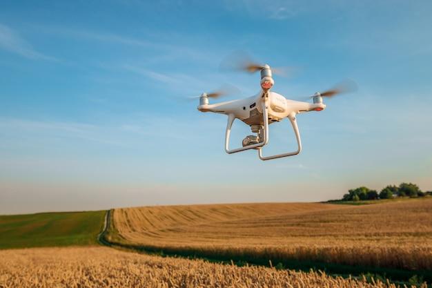 緑のトウモロコシ畑にドローンクアッドヘリコプター