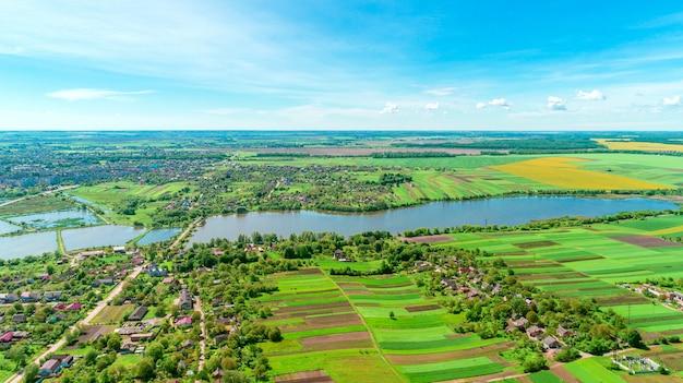 晴れた春の日の田園風景の平面図です。家と緑の野原。ドローン写真
