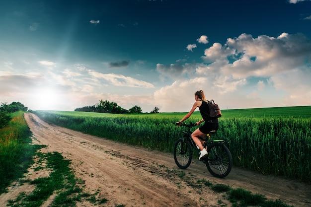 フィールドに夕日をバイカーの女の子