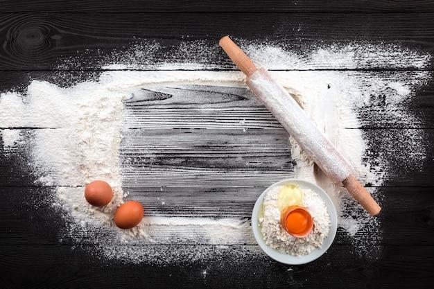 小麦粉と黒いテーブルの上の食材。上面図