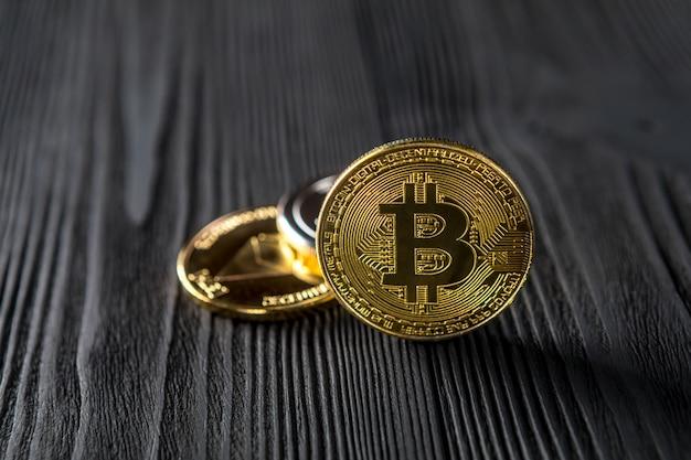 Серебряные и золотые монеты с биткойнами, пульсациями и символом эфириума на дереве.