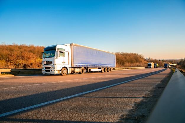 夕暮れ時の農村景観における道路上の白いトラックの到着