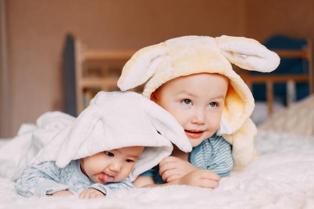 Портрет малыша мальчика и девочку носить кроличьи уши улыбается.