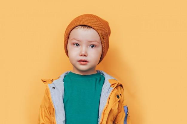 秋の時間。手に黄色の葉で笑顔の赤ちゃん。季節のファッション。秋の服。キッズファッション。葉が落ちる。黄金の服、オレンジ色の帽子の少年