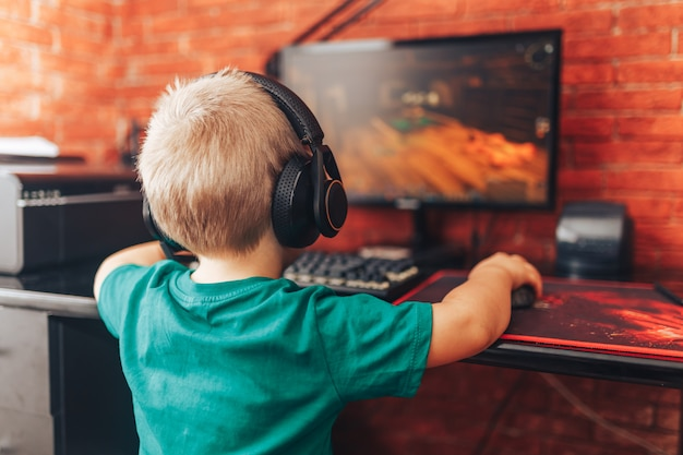 Маленький мальчик, играя в игры на компьютере в наушниках с микрофоном, компьютерная игра