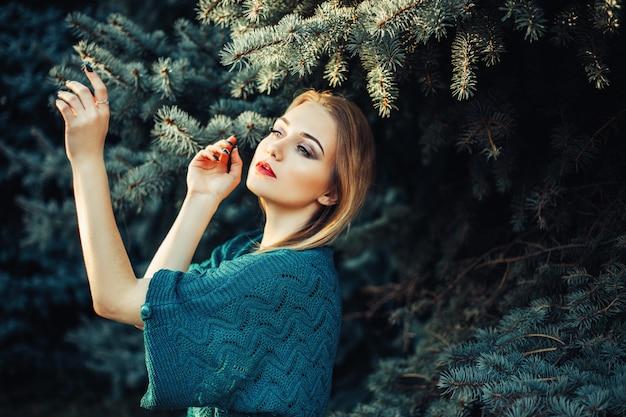 緑の青いモミの木の近くの公園で緑のセーターにブロンドの髪と青い目を持つ少女