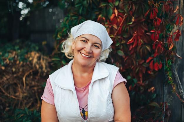 成熟した笑顔の女性庭師または彼女の頭にスカーフで庭に座っている女性