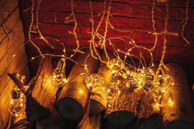 木製の薪ロフトデザインの暖炉で横になっている装飾クリスマスクリスマスライト電球