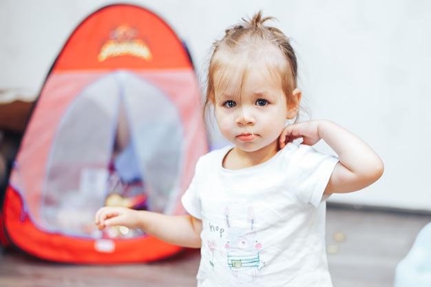 Маленькая девочка играет в игрушки дома в белой футболке