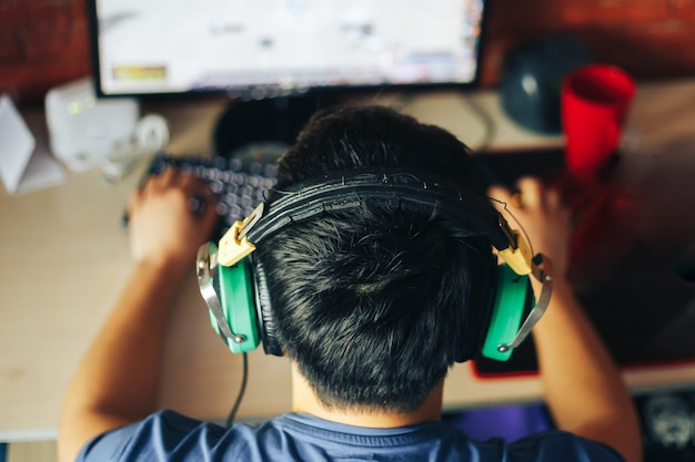 若い男がコンピューターでゲームをプレイ
