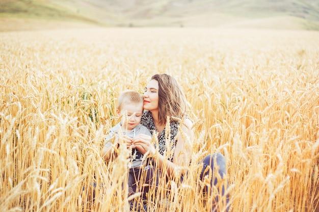 若くて美しい女性が小麦の牧草地で彼女の幼児の赤ちゃんと遊ぶこと。夏のコンセプトです。