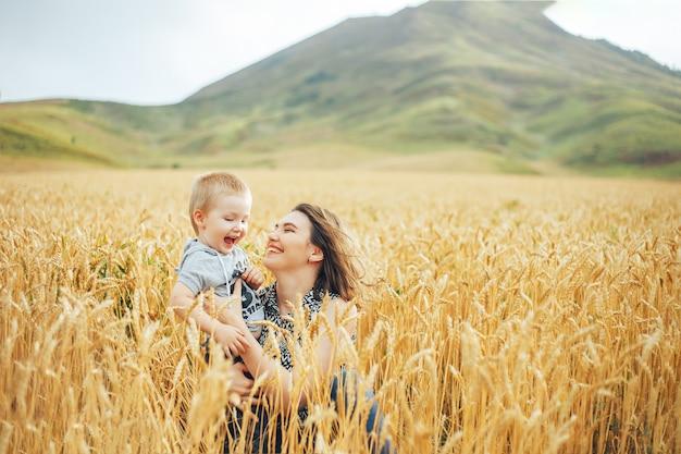 若くて美しい女性が小麦の牧草地で彼女の幼児の赤ちゃんと遊ぶこと。
