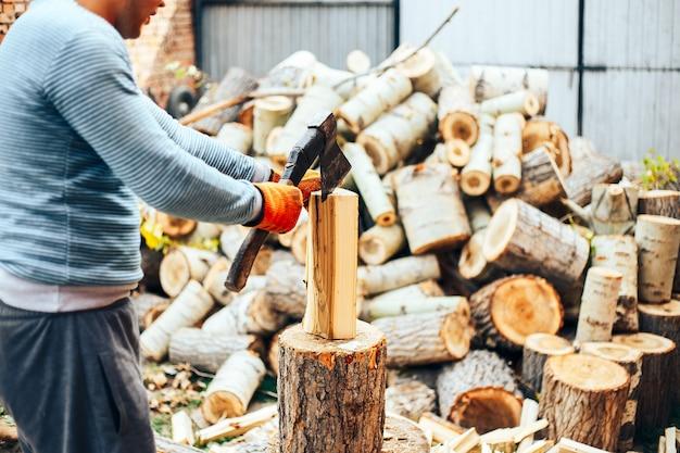 ジーンズと市松模様のシャツの手で斧で切り株の近くに立っている男