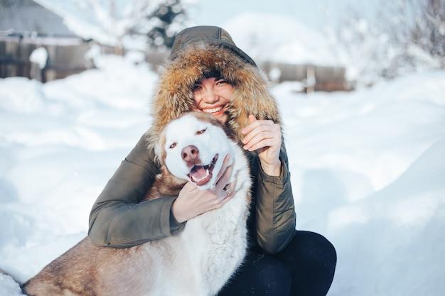 Молодая женщина играет с собакой рыжий хаски