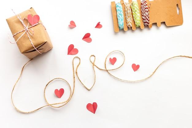 白い背景の上のビンテージバレンタインデーギフトボックス。ピンクの紙の弓、ジュートロープ、ラブレター