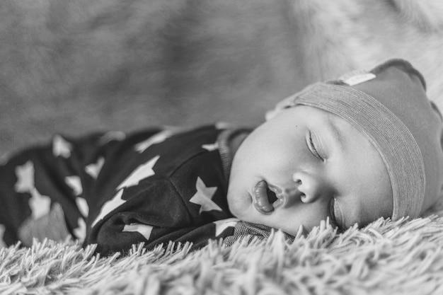 黒と白の帽子のノイズ画像で毛布の上に寝ている生まれたばかりの赤ちゃん